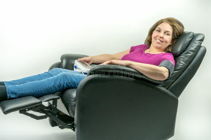 Wiek średni kobieta oparta w czarnym rzemiennym recliner karle z powrotem Sprawdzać ciśnienie krwi używać przenośną ciśnienie krw obrazy royalty free