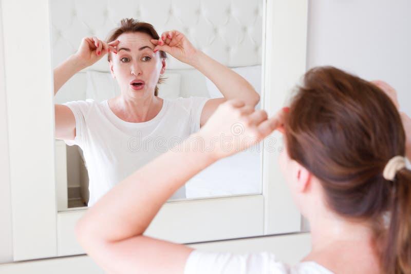 Wiek średni kobieta patrzeje w lustrze na twarzy zmarszczenia czole w sypialni Zmarszczenia i anty starzenie się skóry opieki poj zdjęcia stock