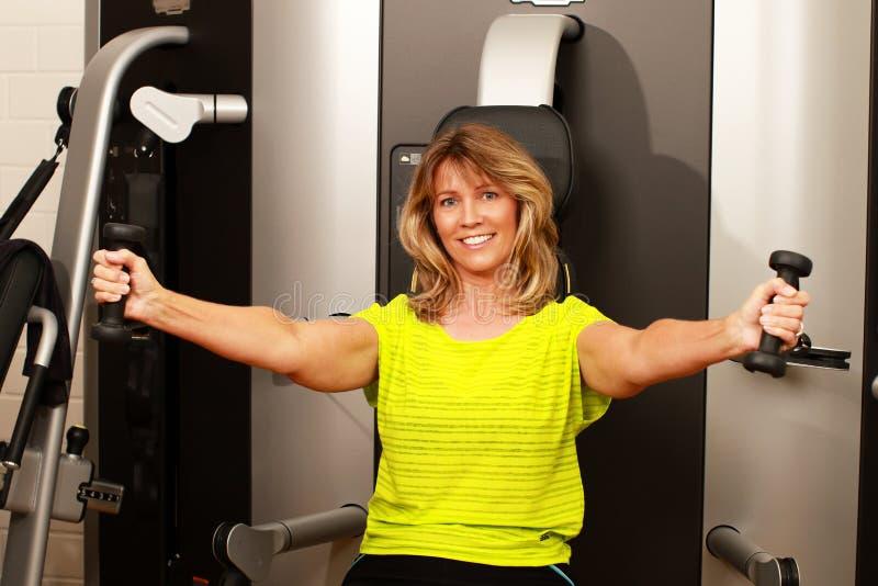 Wiek średni kobieta używa ciężaru lifter dla ona ręki obraz stock