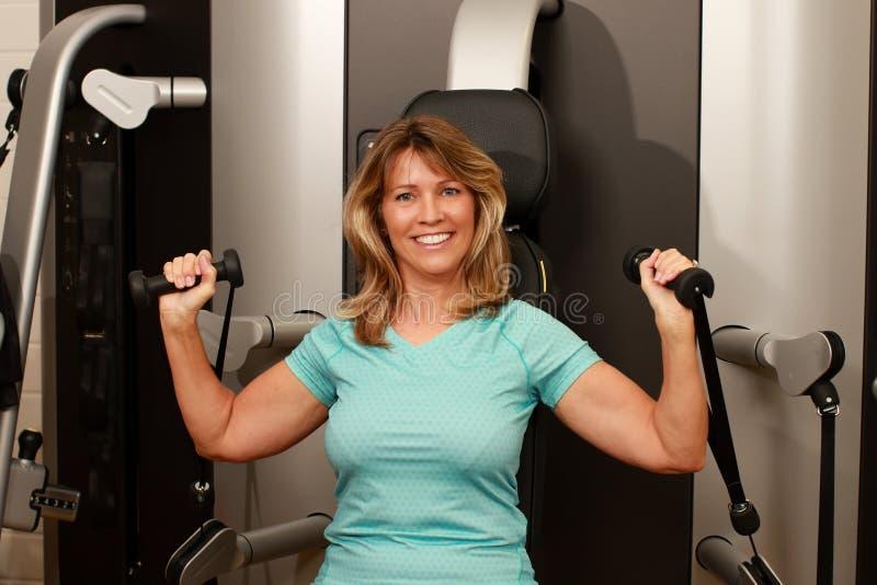 Wiek średni kobieta używa ciężaru lifter dla ona ręki obraz royalty free