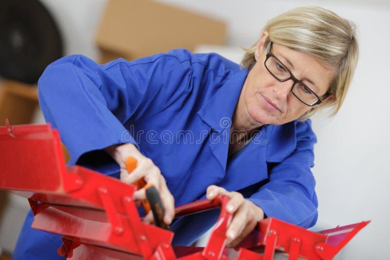 Wiek średni kobieta w coveralls robi naprawom z pudełkiem obrazy stock