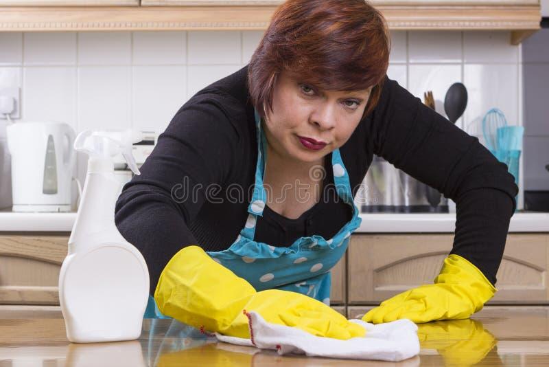 Wiek średni kobiety okurzanie w kuchni zdjęcia stock