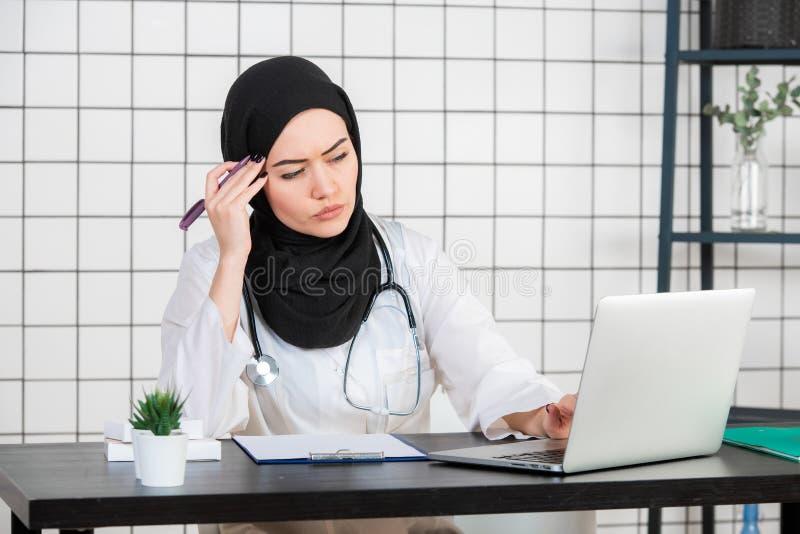 Wiek średni pielęgniarki starsza arabska kobieta jest ubranym hijab przy medycznym biurem z ręką na podbródku myśleć o pytaniu, z obraz stock