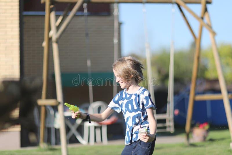 Wiek chłopiec bawić się z wodną krócicą fotografia stock