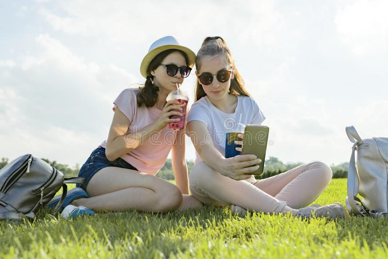 Wiek dojrzewania dziewczyny w kapeluszu i okularach przeciwsłonecznych na zielonym gazonie w odtwarzanie parku cieszy się ich kok fotografia stock