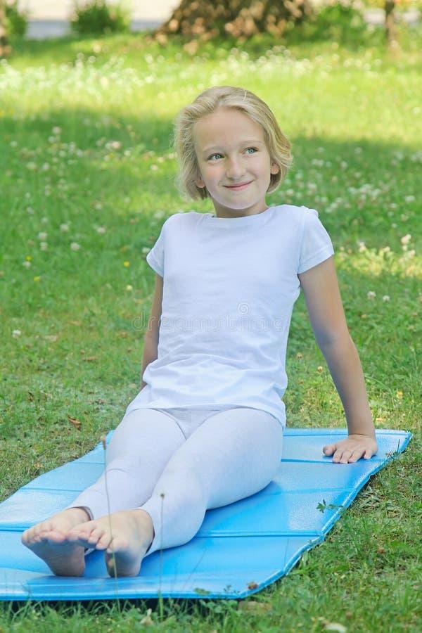 Wiek dziewczyna w świetle odziewa odpoczynki i sztuki bawją się na macie w parku fotografia stock
