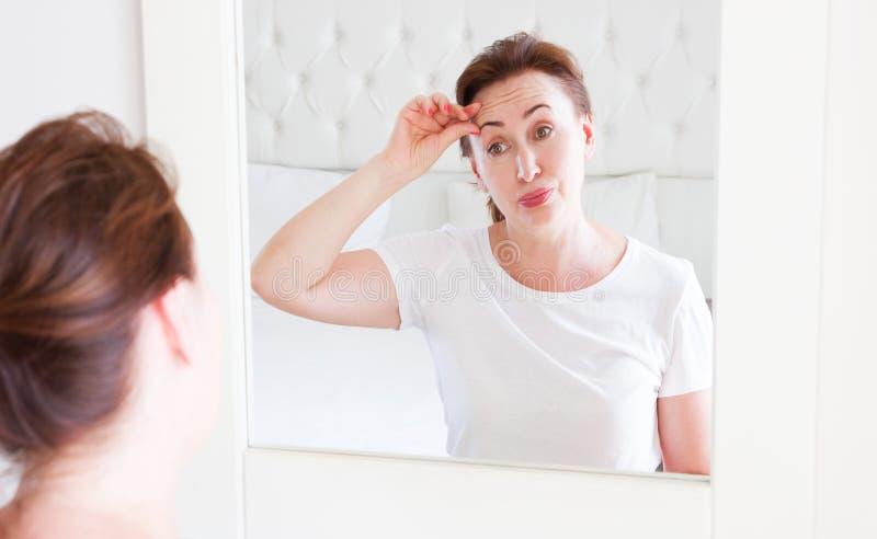 Wiek ?redni kobieta patrzeje w lustrze na twarzy zmarszczenia czole w sypialni Zmarszczenia i anty starzenie si? sk?ry opieki poj obrazy royalty free