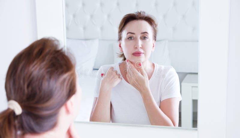 Wiek ?redni kobieta patrzeje w lustrze na zmarszczenie twarzy na czole Przekwitanie, zmarszczenia i anty starzenie si? sk?ry opie obraz stock