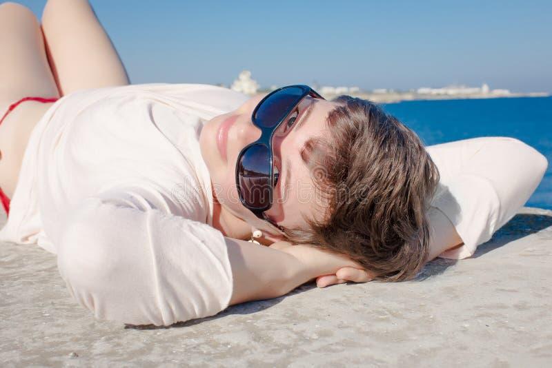 Wieka średniego żeński lying on the beach z rękami za jego głowa obraz royalty free