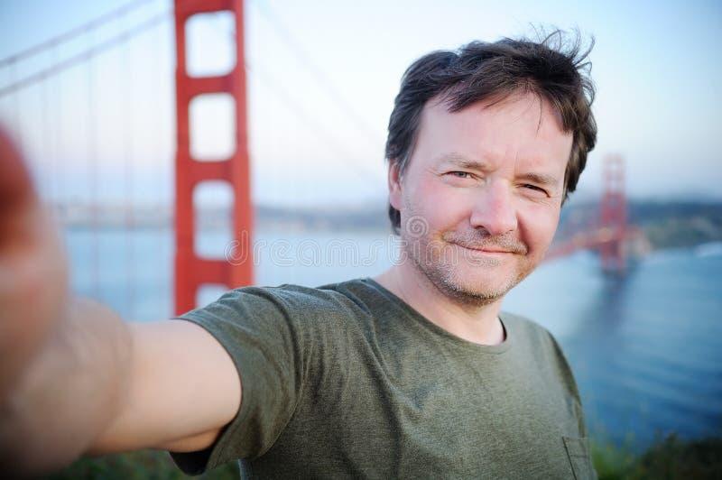 Wieka średniego mężczyzna robi jaźń portretowi z Golden Gate Bridge w San Fransisco zdjęcia stock