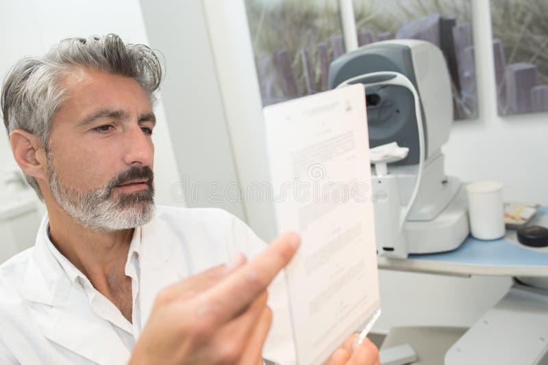 Wieka średniego męskiego okulisty doktorski sprawdza eyechart zdjęcie royalty free