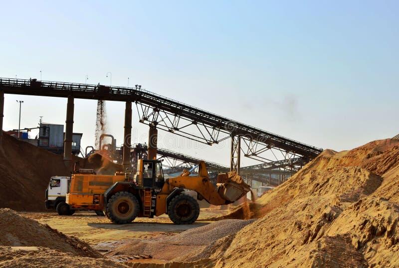 Wiel front-end lader het leegmaken zand in zware stortplaatsvrachtwagen Verpletterend fabriek, machines en materiaal om te verple stock fotografie