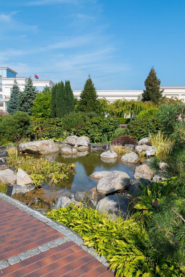Wielcy dekoracyjni kamienie w małym stawie w parku wśród zielonych krzaków zdjęcie stock