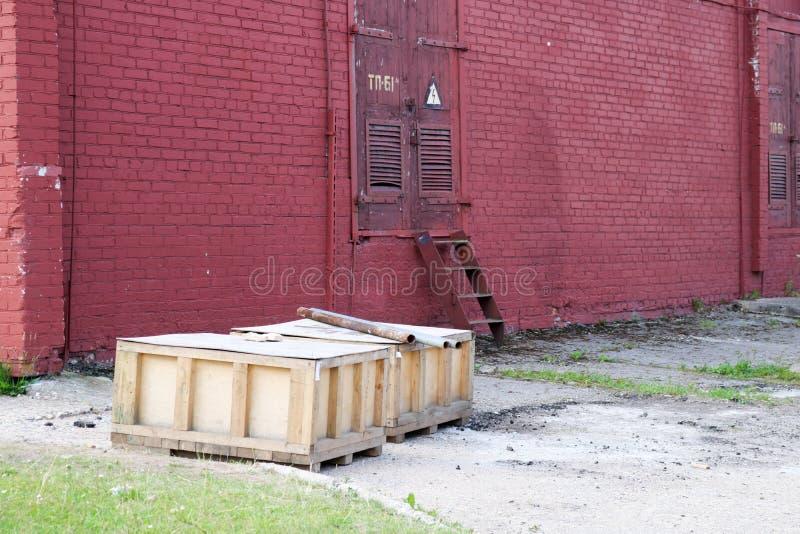 Wielcy drewniani pudełka z towary statywowym outside w na wolnym powietrzu w magazynie przemysłowy przedsięwzięcie przeciw czerwo fotografia stock