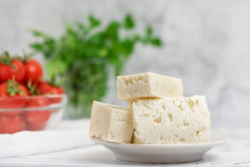 Wielcy kawałki feta ser w biel półkowych i czereśniowych pomidorach na lekkim tle Selekcyjna ostrość, wysoki klucz fotografia stock