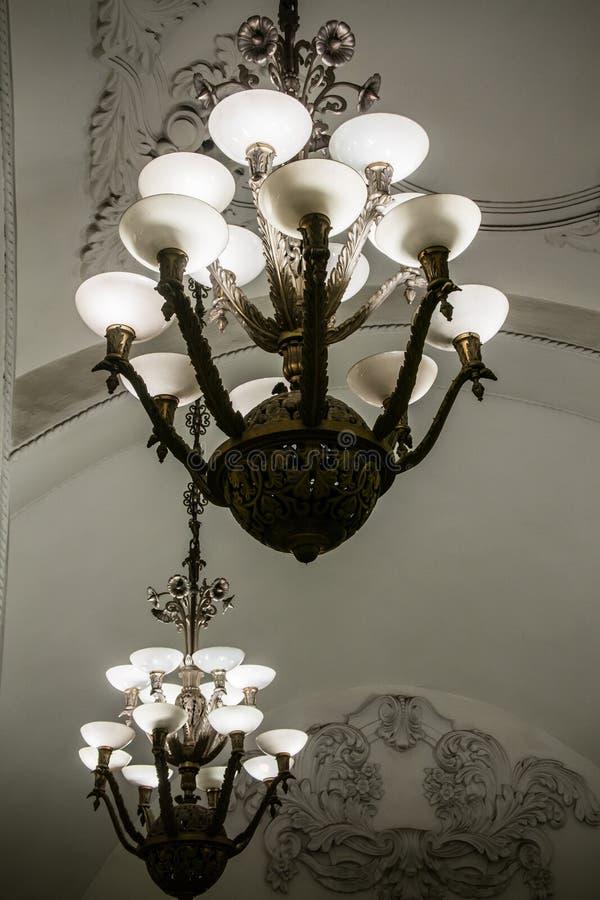 Wielcy luksusowi świeczniki pod ornamentacyjnym łukowatym sufitem zdjęcie stock