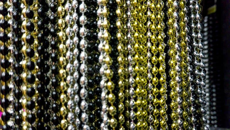 Wiele czarni, biali, srebni, złociści i złoci koraliki, bawją się neacklaces dla nowego roku tła lub świętowań makro- zakończenie zdjęcie royalty free