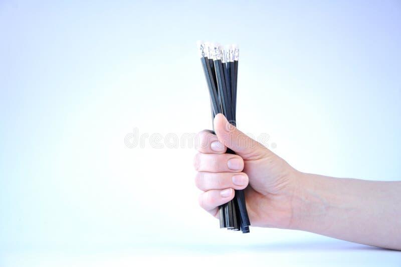 wiele czarni ołówki w ręce na białym tle obraz stock