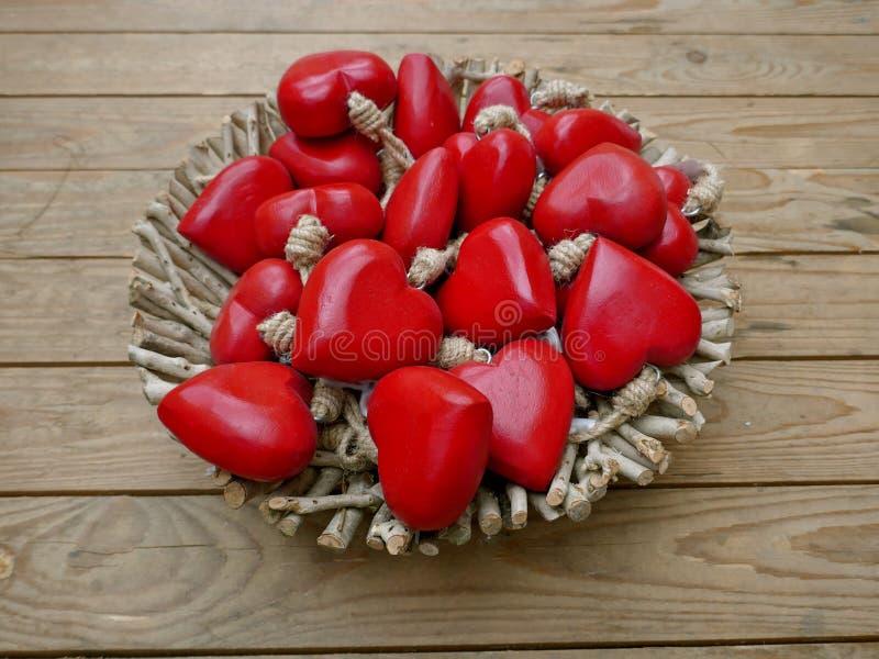 Wiele czerwoni serca w koszu przed brown deski ścianą zdjęcie stock