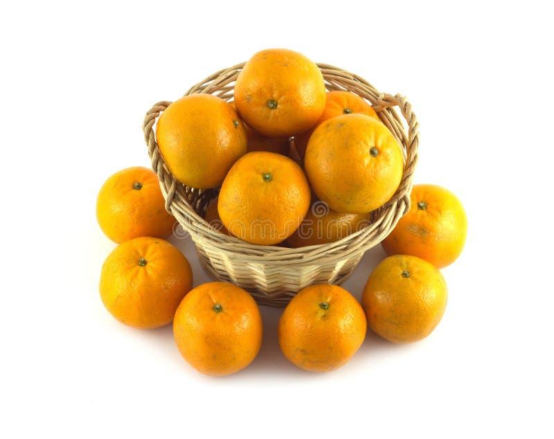 Wiele dojrzałe pomarańcze w brown łozinowym koszu i zbliżają je odizolowywającego obraz stock