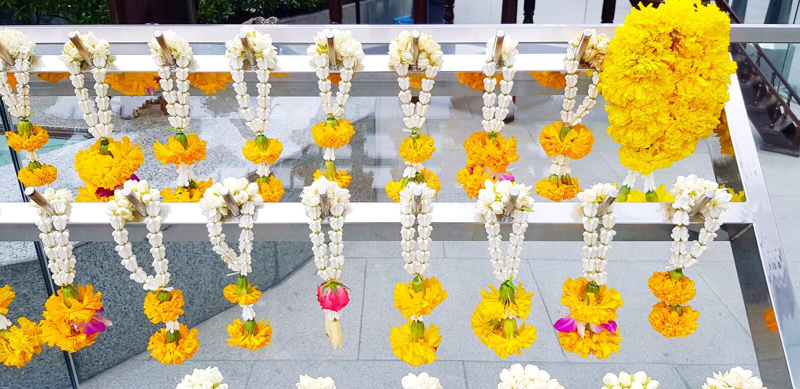 Wiele girlanda kwiatu obwieszenie na białym stal nierdzewna wieszaku dla cześć Buddha obrazy royalty free