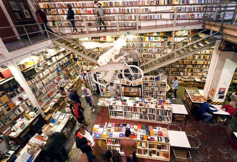 Wiele klienci wśrodku bookstore Ler Devagar z wysokimi półkami na książki wokoło i grafika obrazy stock