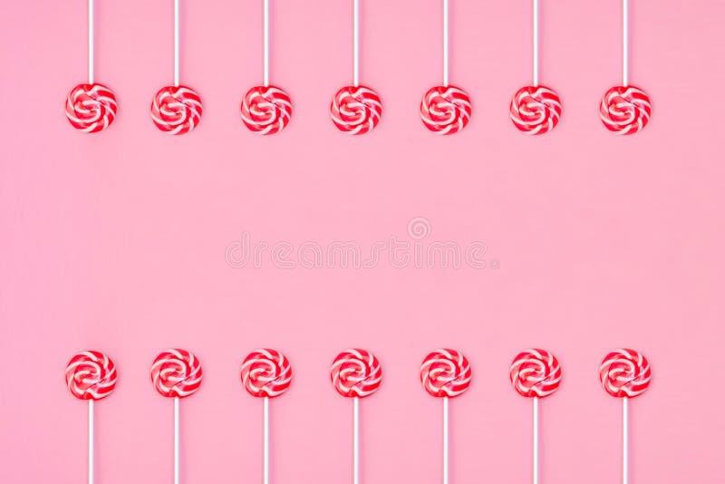 Wiele kolorowi lizak?w candys uk?adaj?cy w dwa grupach i opr??niaj? przestrze? w centrum na r??owym tle zdjęcia stock