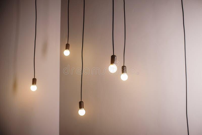 Wiele lampy na długim obwieszeniu i sznurze zaświecają w pokoju obraz royalty free