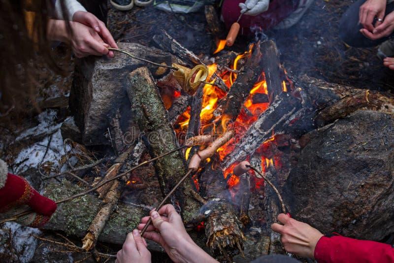 Wiele ludzie smażą kiełbasy i bliny na ogieniu podczas pinkinu w zimie obraz stock