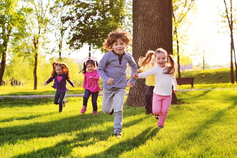 Wiele młode dzieci uśmiecha się biegać wzdłuż trawy w parku obraz stock