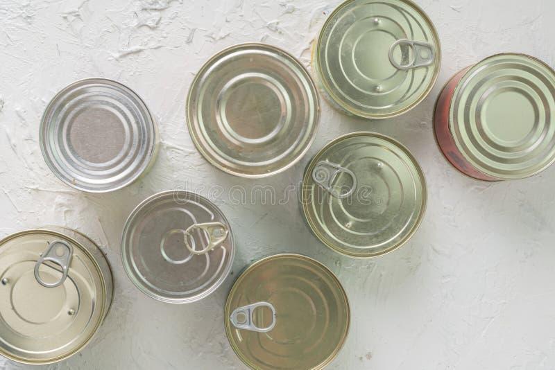 Wiele nieotwarte blaszane puszki z posiłkami tak jak mięso i ryba na stole, chroniący foods fotografia royalty free