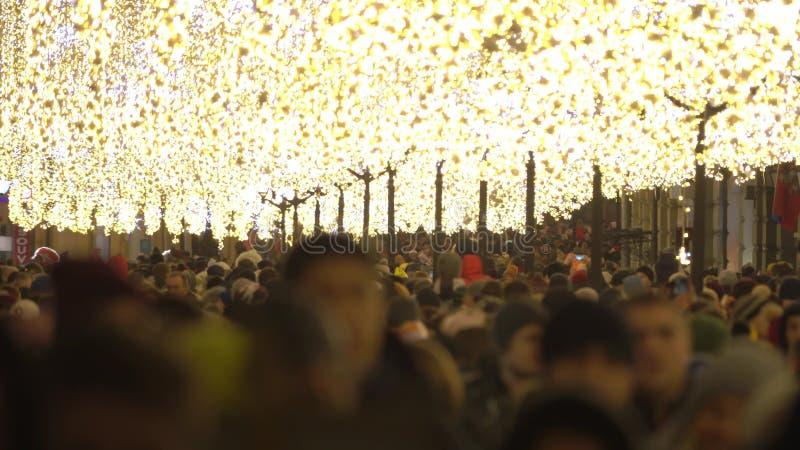 Wiele niewiadomi ludzie chodzą wzdłuż zwyczajnej ulicy dekorującej dla bożych narodzeń i nowego roku obrazy stock