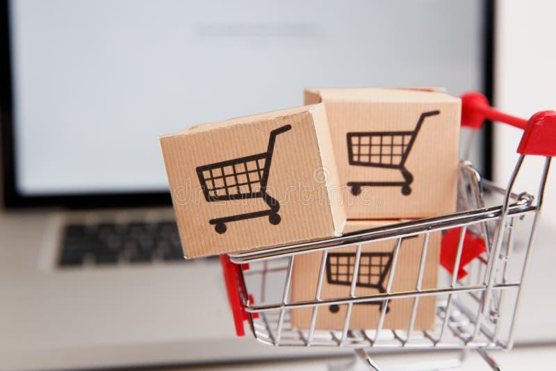 Wiele papierowi pudełka w małym wózku na zakupy na laptop klawiaturze Pojęcia o online zakupy który kupować mogą konsumenci obraz royalty free