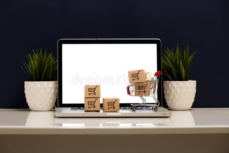Wiele papierowi pudełka w małym wózku na zakupy na laptop klawiaturze Pojęcia o online zakupy który kupować mogą konsumenci zdjęcia stock