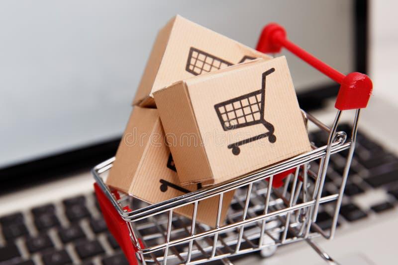 Wiele papierowi pudełka w małym wózku na zakupy na laptop klawiaturze Pojęcia o online zakupy który kupować mogą konsumenci zdjęcie royalty free