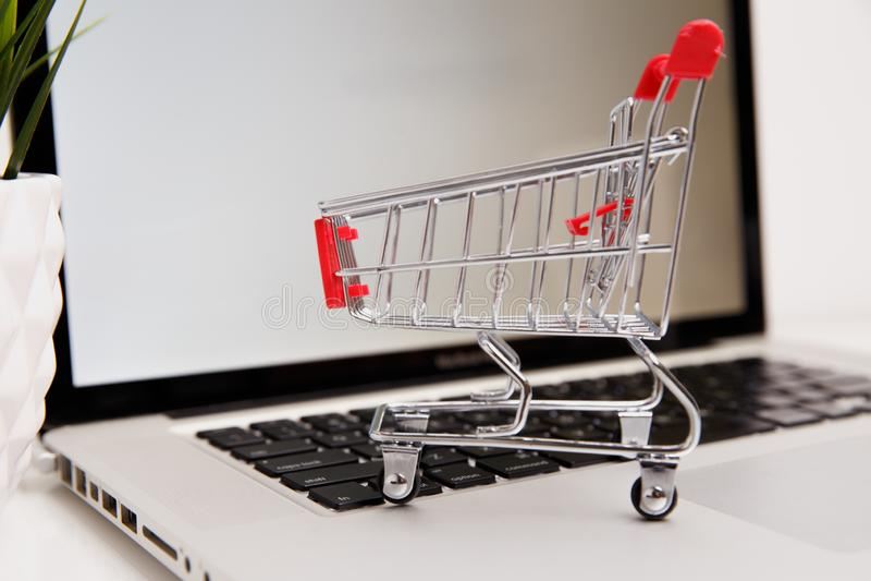 Wiele papierowi pudełka w małym wózku na zakupy na laptop klawiaturze Pojęcia o online zakupy który kupować mogą konsumenci zdjęcia royalty free