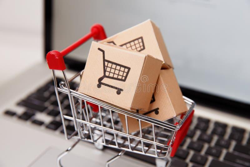 Wiele papierowi pudełka w małym wózku na zakupy na laptop klawiaturze Pojęcia o online zakupy który kupować mogą konsumenci fotografia royalty free
