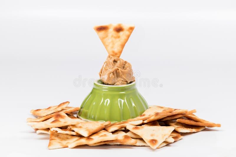 Wiele pita krakers i dap masło orzechowe z zielonym pucharem obrazy stock