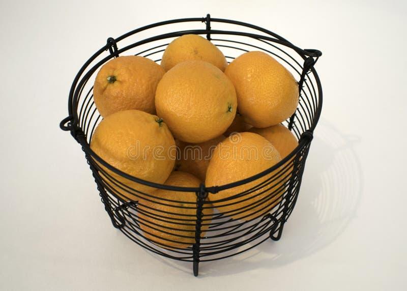 Wiele pomarańcze w czarnym metalu koszu na bielu ukazują się zdjęcia stock