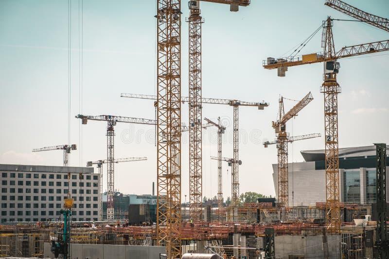 Wiele pracownicy budowlani na budowie i żurawie fotografia royalty free