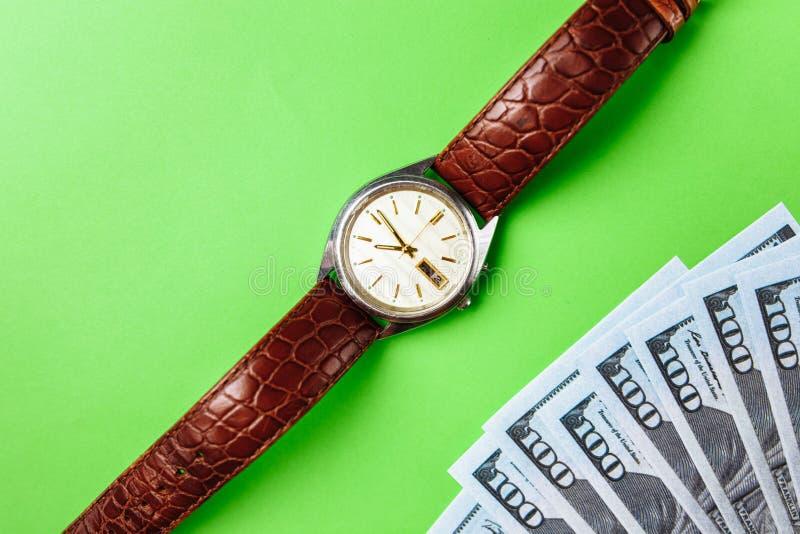 Wiele rachunki 100 dolarów, my banknot, zielony tło z pieniądze gotówki waluty zakończeniem, pojęcie czas warty pieniądze, zegar obraz royalty free