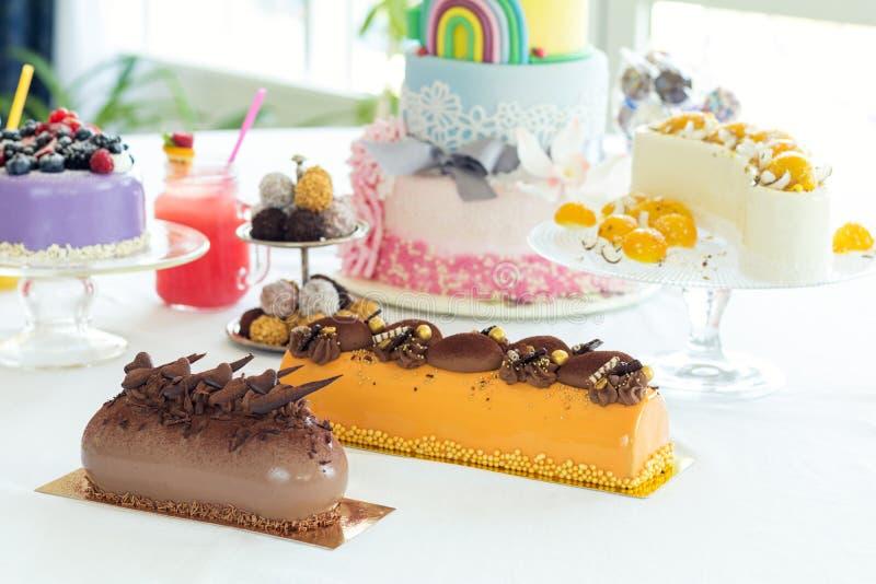 Wiele słodcy ciasta na bielu stole z świeżymi lato jagodami fe fotografia stock