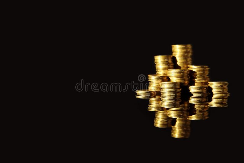 Wiele sterty monety na lustrze ukazują się przeciw czarnemu tłu obrazy stock