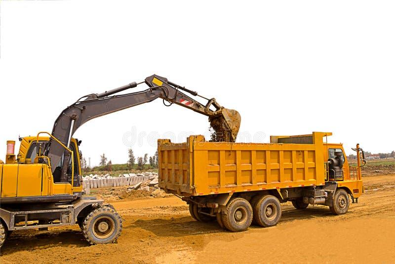 Wielgraafwerktuig en stortplaatsvrachtwagen met witte achtergrond, wielgraafwerktuig in bouwwerf, grond stock afbeeldingen