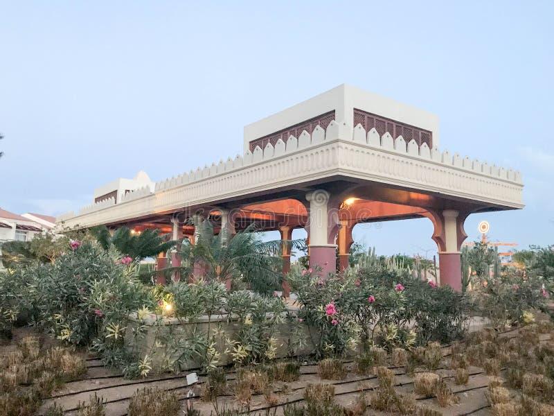 Wielka biała struktura z kolumnami i łuki w meksykaninie i języku arabskim projektujemy pod niebem, przeciw tłu zielony kaktus fotografia royalty free