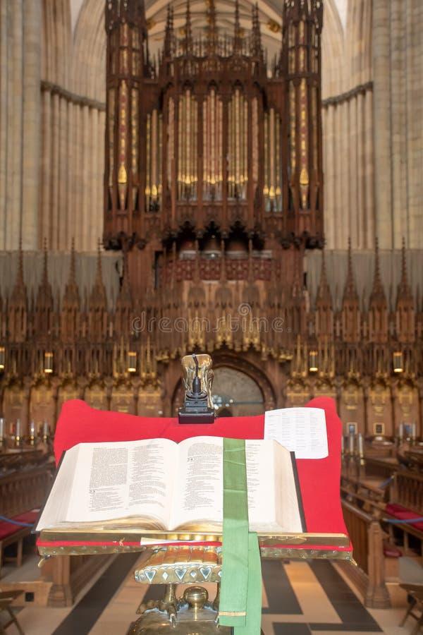 Wielka biblia otwarta w ambonie z wielkim kościół w tle obraz stock