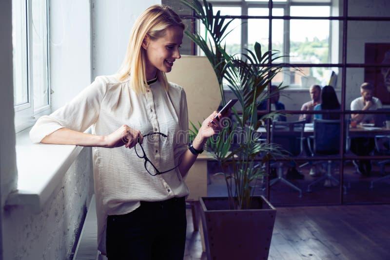 Wielka biznesowa wiadomość Boczny widok rozochocony młody piękny bizneswoman w szkłach używać jej mądrze telefon z uśmiechem zdjęcia stock