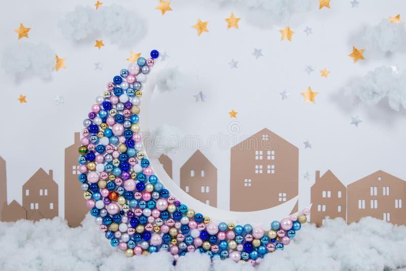 Wielka dekoracyjna księżyc dekorował z Bożenarodzeniowymi stubarwnymi piłkami na tle chmury fotografia royalty free