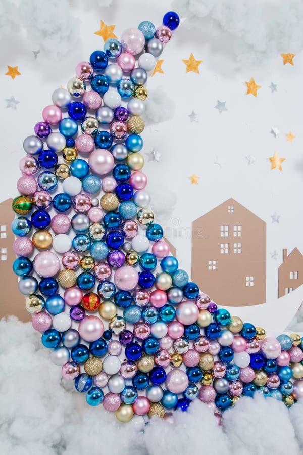 Wielka dekoracyjna księżyc dekorował z Bożenarodzeniowymi stubarwnymi piłkami na tle chmury zdjęcie royalty free