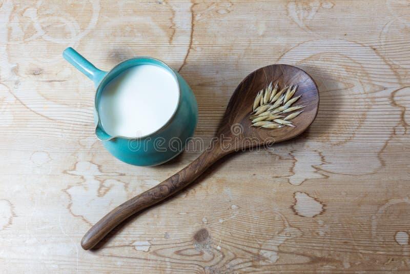 Wielka drewniana łyżka z owsami obok ceramicznego pucharu miotacza owsa mleko na nieociosanym drewno stołu tle obraz royalty free
